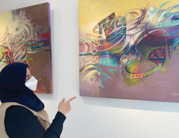 الجشي مع إحدى لوحاتها (اليوم)